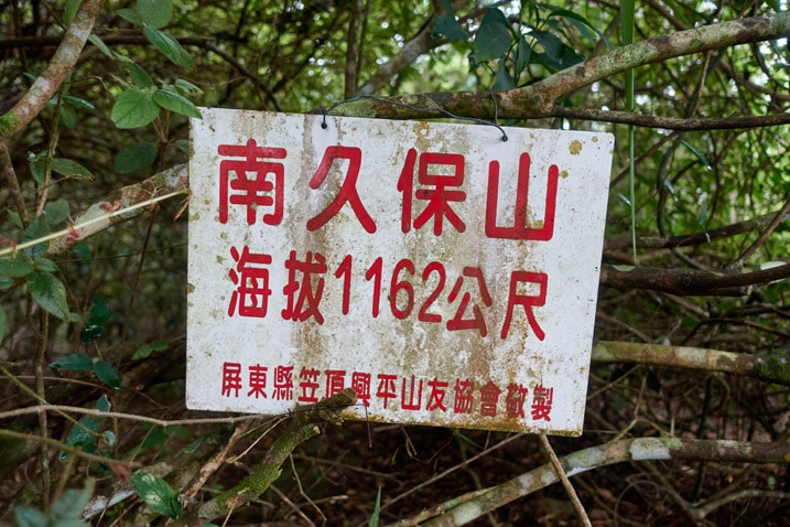 White sign with red chinese letters for NanJiuBaoShan 南久保山