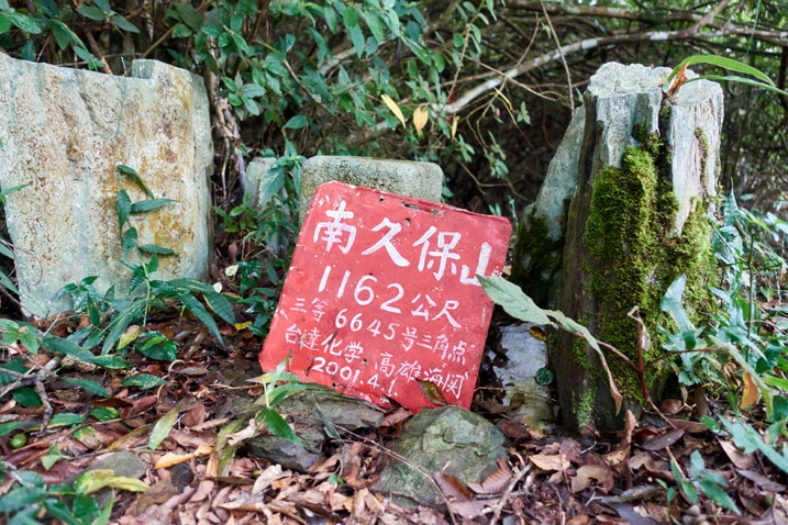 Red sign with white chinese letters leaning against a stone for NanJiuBaoShan 南久保山