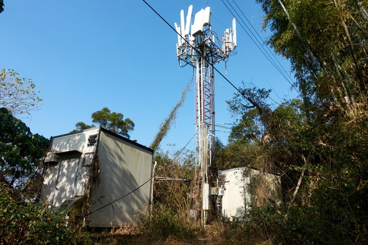 Cellphone tower and supporting equipment nearby - blue sky
