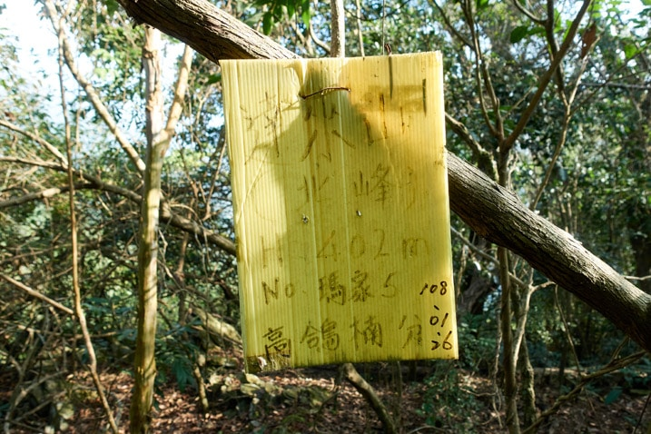 Yellow sign with Chinese writing attached to a tree