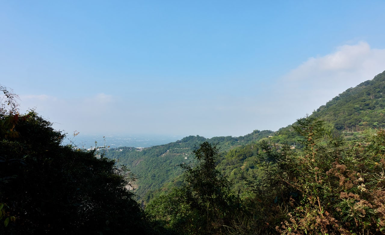 Looking out from a mountain ridge - blue sky - mountains and homes beyond