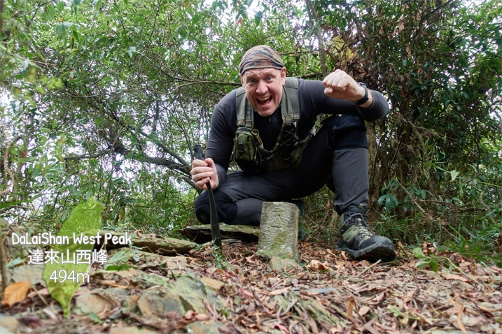 Man with machete kneeling triumphantly behind triangulation stone of DaLaiShan West Peak - 達來山西峰