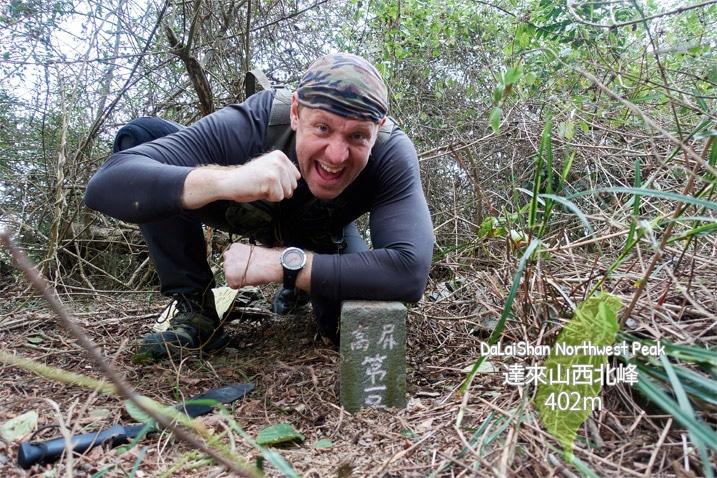 Man kneeling behind stone peak marker of DaLaiShan Northwest Peak - 達來山西北峰 in triumphant pose