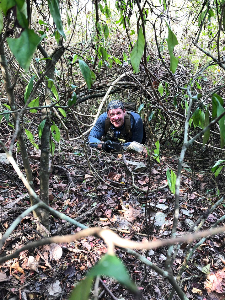 Man crawling under mountain overgrowth
