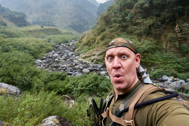 Man taking a selfie with small, rocky riverbed behind him