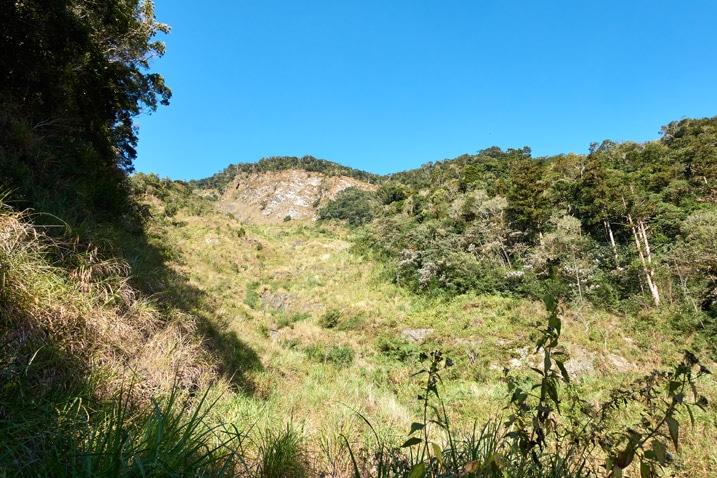 Looking up at mountainside - old landslide - blue sky
