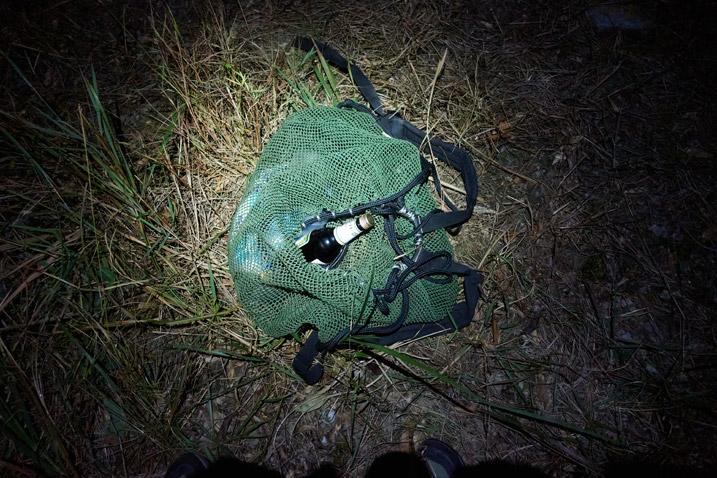 Green mesh bag on ground in the dark - flashlight illuminating - bottle sticking out of bag