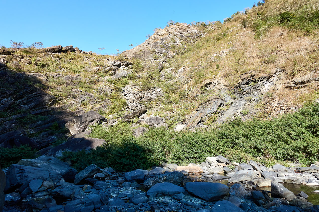 Looking up at mountain landslide - blue sky - rocky riverbed at bottom