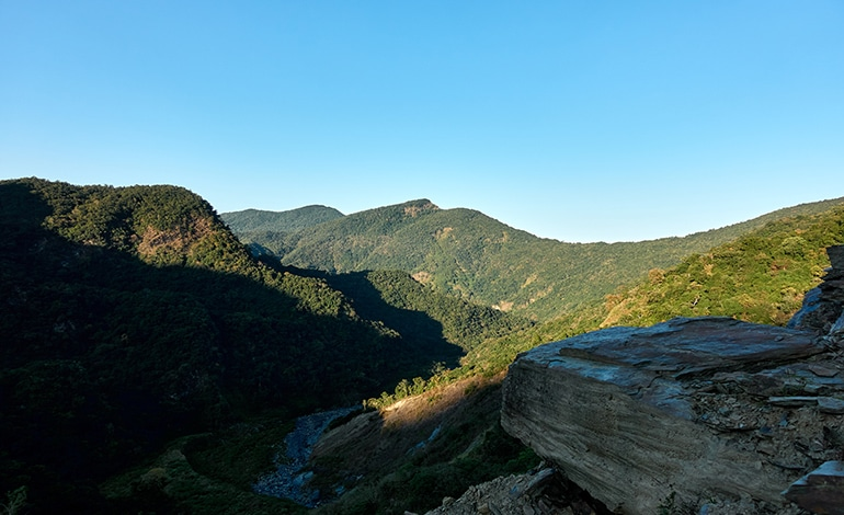 landscape picture of mountains with blue sky - river below - large boulder at bottom right