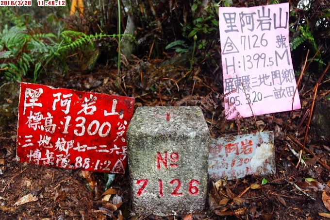 Triangulation stone with three signs lined up next to it