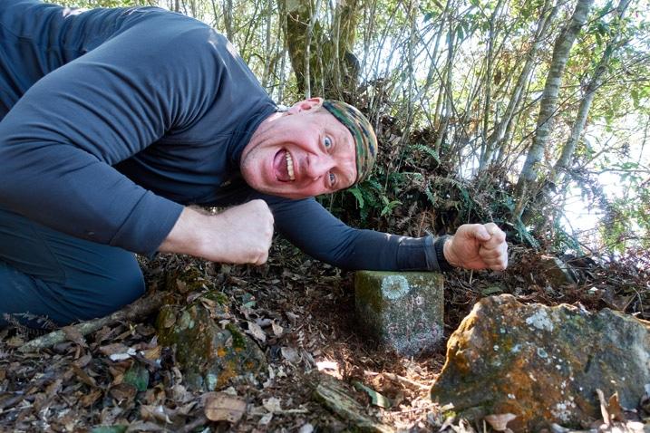 Man kneeling triumphantly next to triangulation stone of LiAYanShan - 里阿岩山