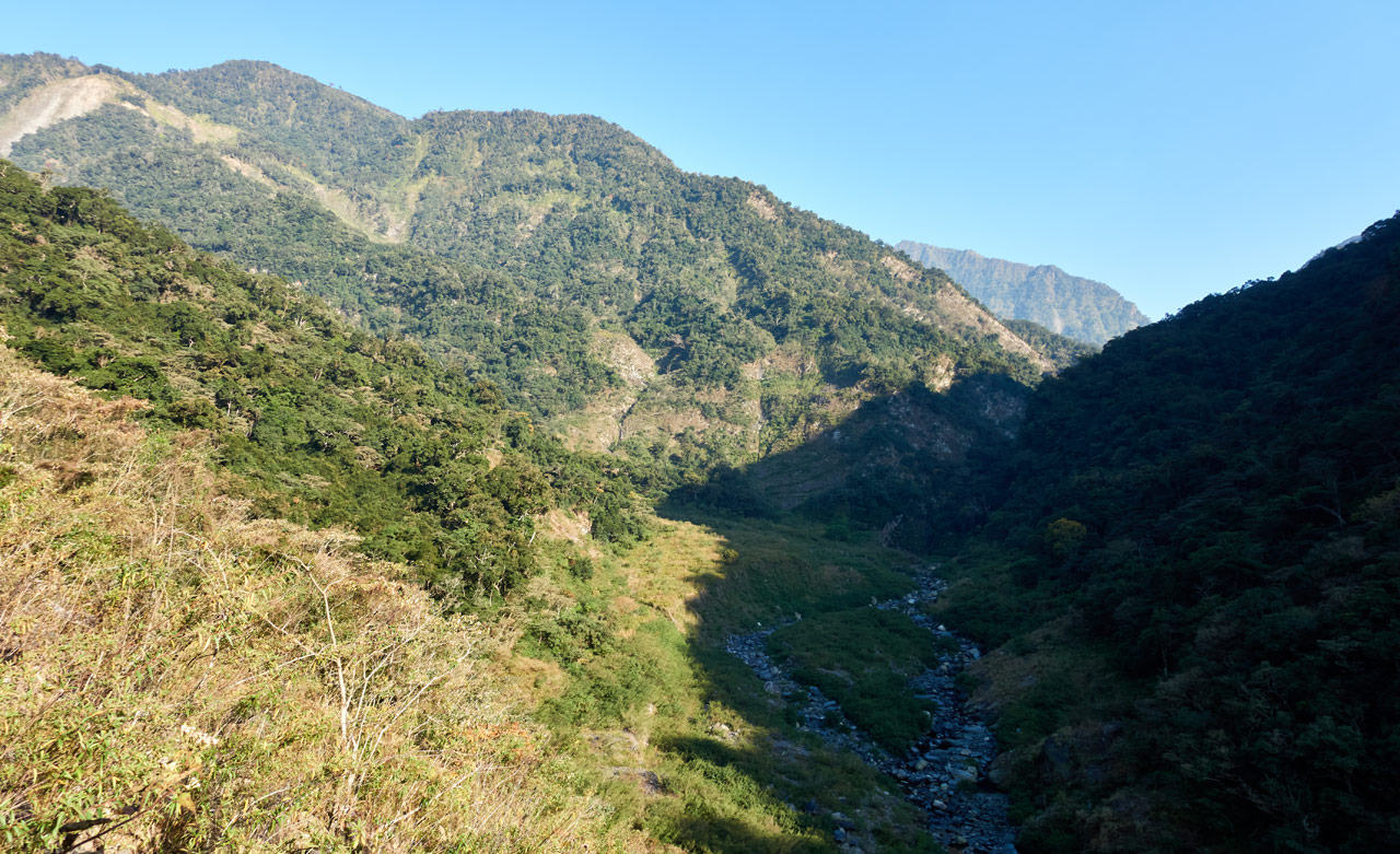 Looking down at small riverbed - mountains in the distance - blue sky
