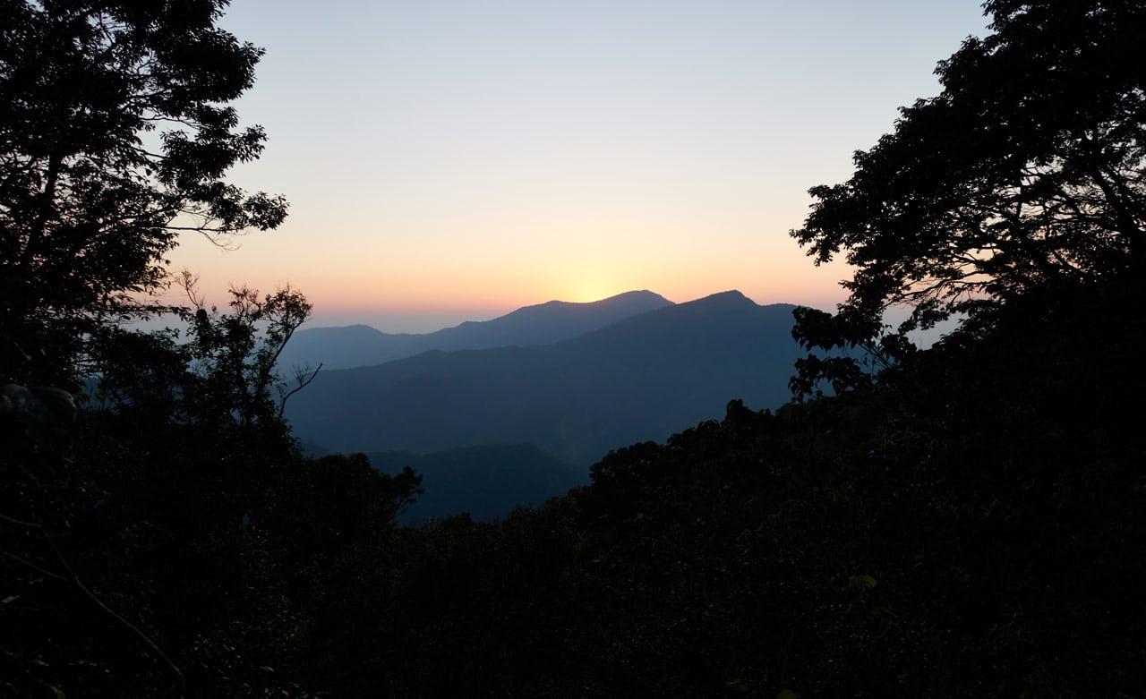 Sun setting behind mountain range - trees in foreground, black