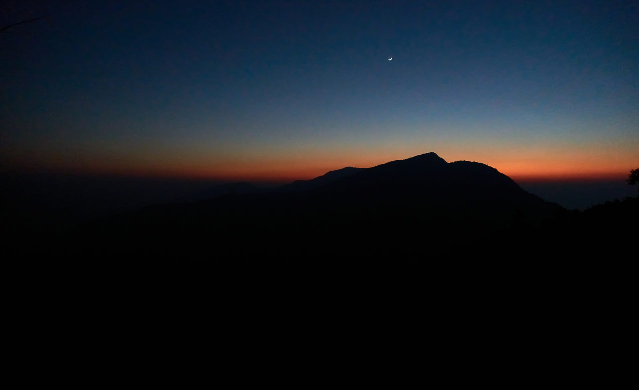 Night picture of mountain range - clear sky with moon above - a bit of orange light in distance