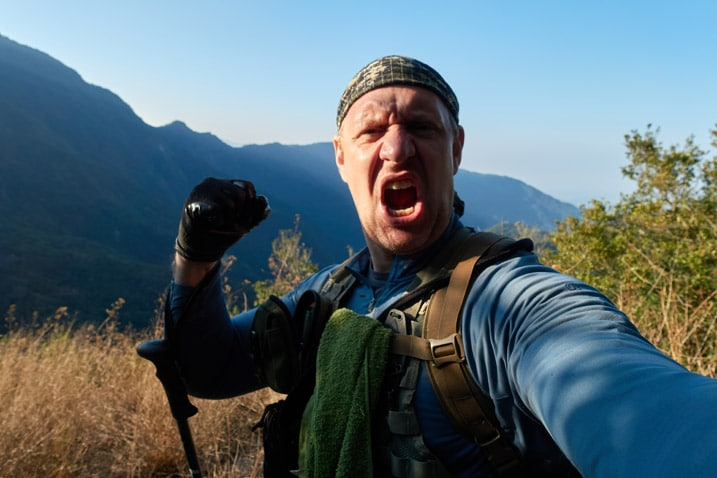 Man yelling triumphantly for some reason - hand in fist - mountains and blue sky in background