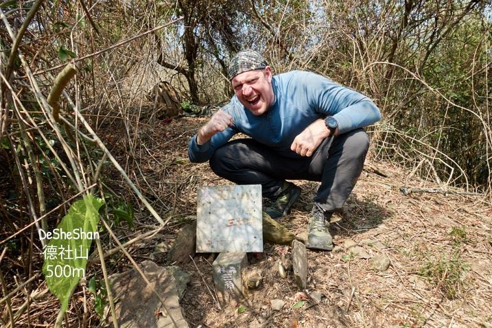 Man posing triumphantly behind triangulation stone for DeSheShan - 德社山