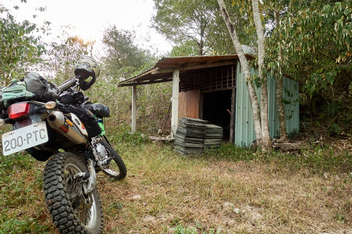 Motorcycle parked near a small shack on mountain